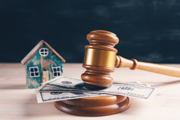 木製の背景にガベルと家を裁判官。離婚の場合の不動産オークションまたは家の分割の概念。