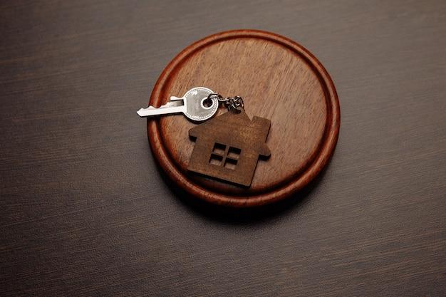 Судейский молоток и брелок в форме двух разделенных частей дома на деревянном