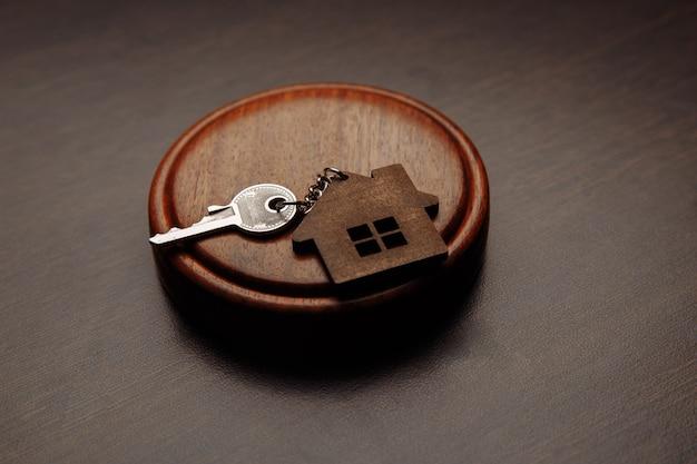 Судейский молоток и брелок в виде двух разделенных частей дома на деревянном.
