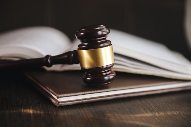 Судейский молоток и юридическая книга о деревянном столе, концепции справедливости и права