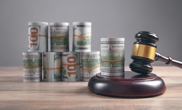 裁判官のガベルとお金は木製のテーブルに転がります。