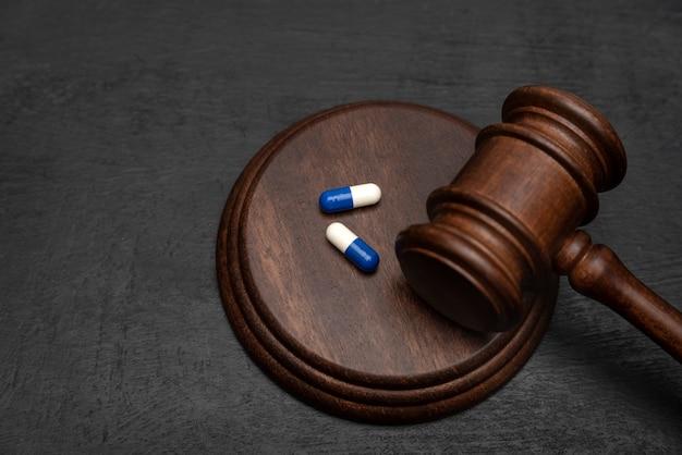 裁判官の小槌と錠剤。医薬品における訴訟医療関連ヘルスケア。医学の法律。