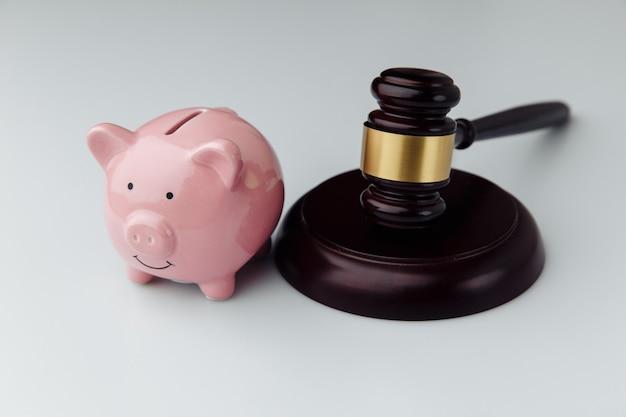 흰색 책상에 판사 망치와 핑크 돼지 저금통. 대출 및 금융 개념