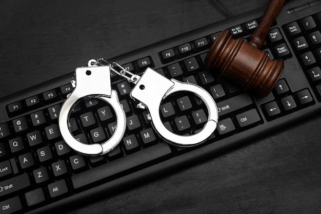 컴퓨터 키보드에 판사 디노와 경찰 수갑. 사이버 범죄 개념입니다. 온라인 불법 복제.