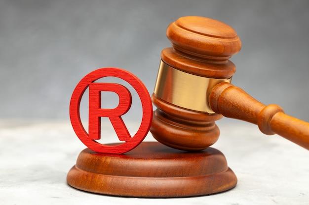 Молоток судьи и красный знак товарного знака.