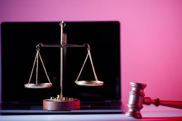 판사 망치와 분홍색 배경의 노트북에 있는 정의의 저울. 법률 개념입니다.