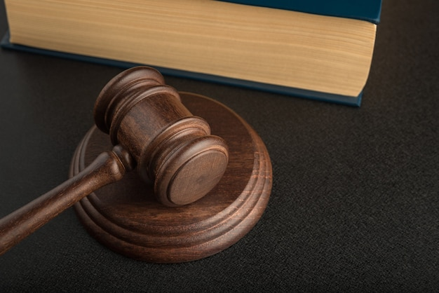 バックグラウンドでガベルとサウンディングブロックと本を判断します。木製のハンマー。正義と法。