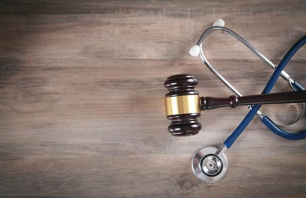 木製のテーブルの上でガベルと聴診器を判断します。