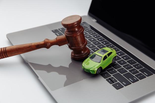 Молоток судьи и игрушечный автомобиль на клавиатуре портативного компьютера. символ закона, справедливости и интернет-аукциона автомобилей.