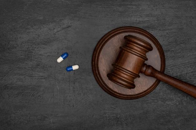 裁判官の小槌と 2 つの錠剤。薬物の不法使用。薬事訴訟。黒い表面。