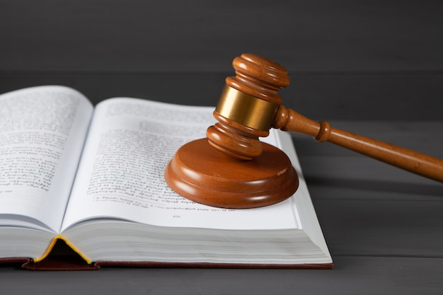 Judge gavel and book on gray surface