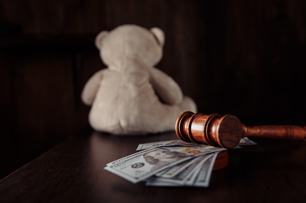 Judge gavel dollar banknotes and teddy bear as a symbol childs rights