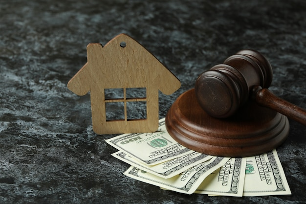 Judge gavel, dollars and wooden house on black smokey table