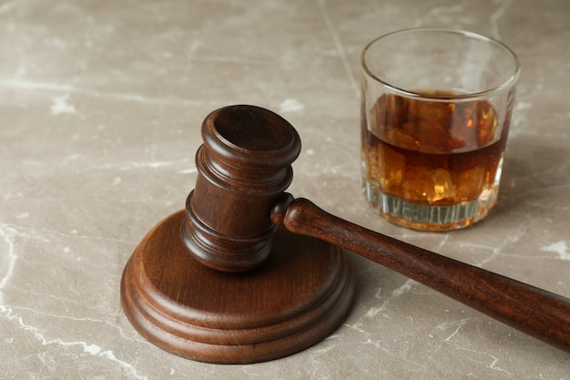 Judge gavel and glass of whiskey on gray textured table