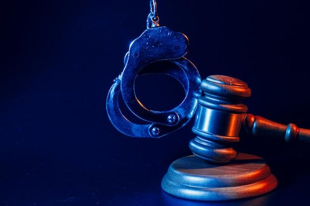 Judge gavel and handcuffs on dark black background