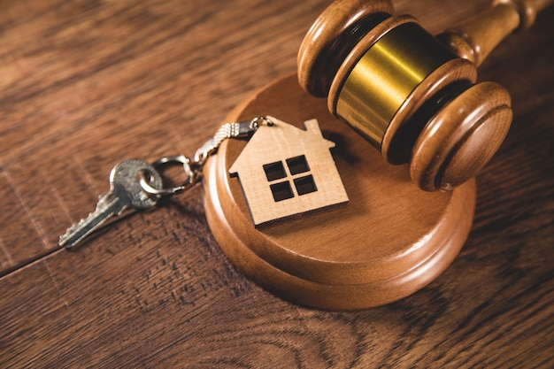 Judge gavel and house key on gray background. estate law concept
