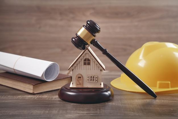 裁判官のガベル、家のモデル、安全ヘルメット、本と文書。