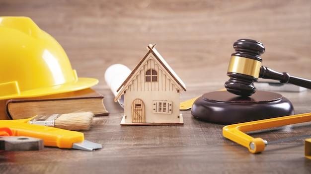 裁判官のガベル、家のモデル、安全ヘルメット、本。