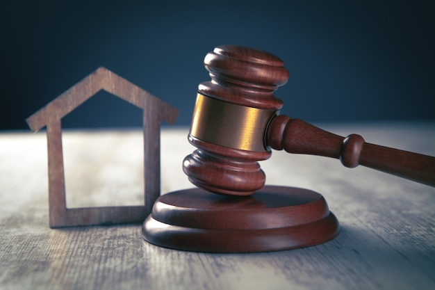 Judge gavel and houses on a wooden background
