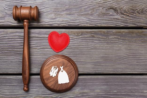 Судья молоток молоток с сердцем и свадебные костюмы. лежащая кожа, вид сверху. серый деревянный фон.