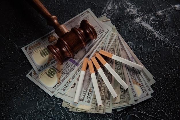 灰色のテーブルに小槌、紙幣、タバコを裁判官。たばこ法