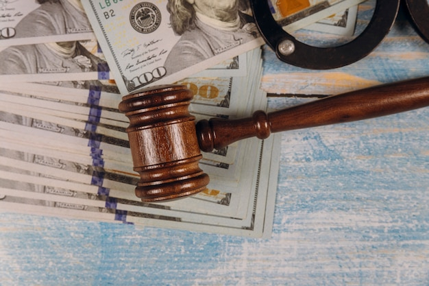 Judge gavel and money on of metal police handcuffs blue wooden table.