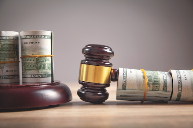 Judge gavel and money rolls on wooden table.