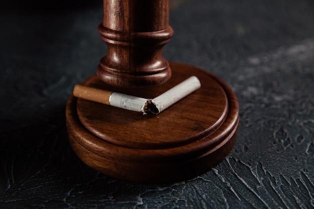 壊れたタバコのクローズアップで小槌裁判官。たばこ法の概念
