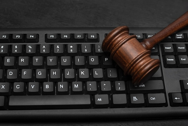 コンピューターのキーボードでガベル裁判官。インターネットオークション。インターネット上の法的責任。