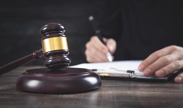テーブルの上の裁判官小槌。裁判官の署名文書。法律の概念