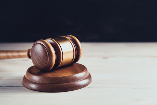 木製の背景にガベル裁判官
