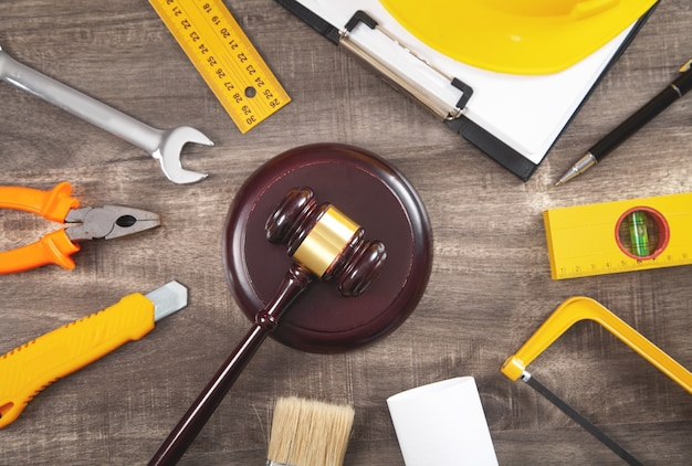 Judge gavel, safety helmet and working tools. construction law
