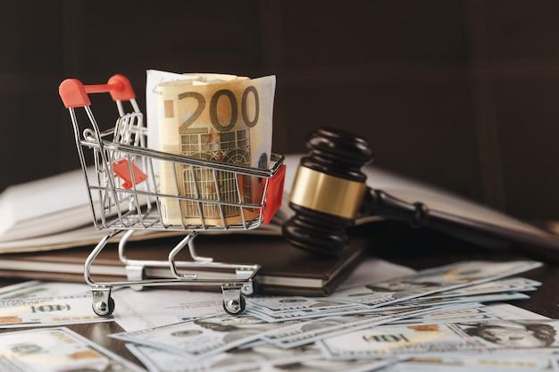 ガベル判事、法廷の判事のテーブルに米ドルと法律の本を使った正義の尺度。保釈、破産、手数料、税金、詐欺、罰金、罰金および金融詐欺のイラストのコンセプト イメージ