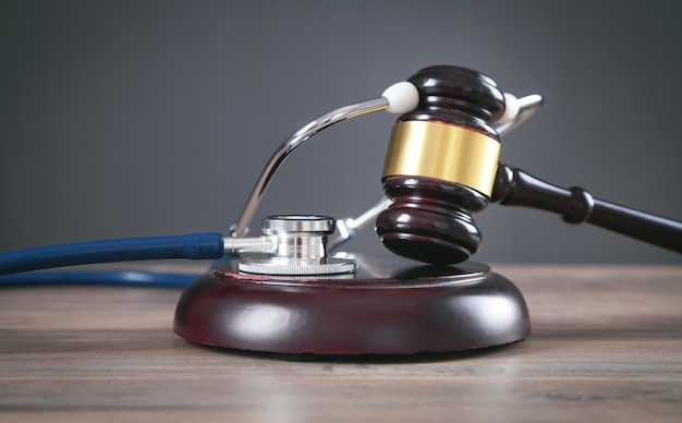 Judge gavel and stethoscope on the wooden table.