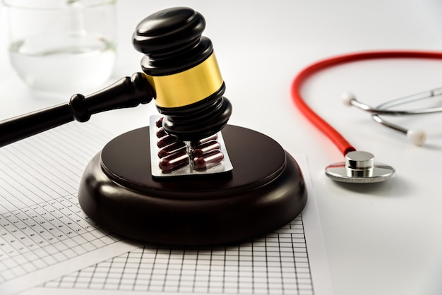 Judge gavel on tablets and pills, sentences a scam from the medical industry.