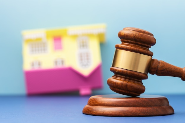 Judge gavel and upsidedown toy house on table real estate arrest concept