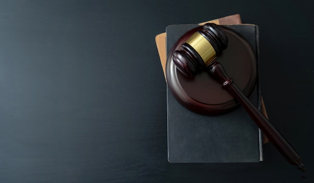木製のテーブルの上の本を持つ裁判官小槌