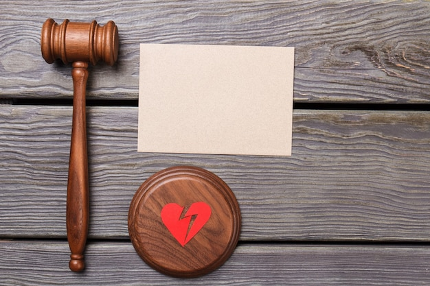 Judge gavel with broken heart. blank paper for copy space. old wooden desk.