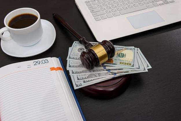 Судейский молоток с долларовыми банкнотами, ноутбуком и кофе
