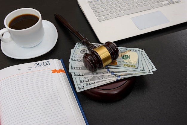 Judge gavel with dollar banknotes, laptop and coffee