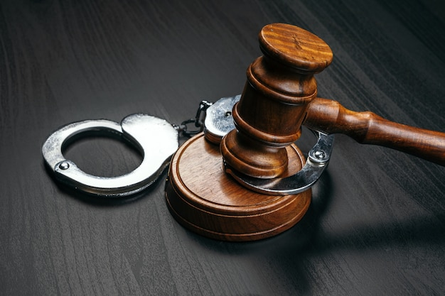 Judge gavel with handcuffs on wooden table