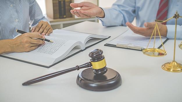 法律事務所のバックグラウンドでチームミーティングを行っている司法弁護士とガベル裁判官。法律および法務サービスの概念。