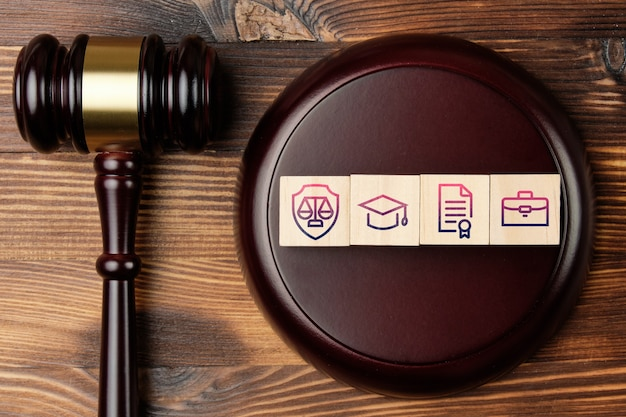 Judge gavel with legal activity concept on abstract wooden blocks with icons.