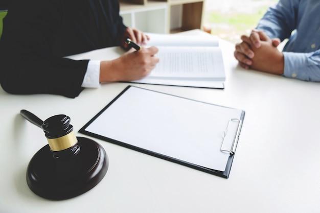 Судейский молоток с юридическими документами, консультирование юристов с деловым человеком