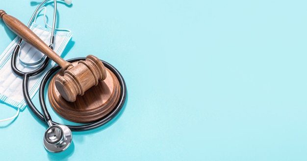 Judge gavel with medical mask and stethoscope on blue background protection of medical rights concept