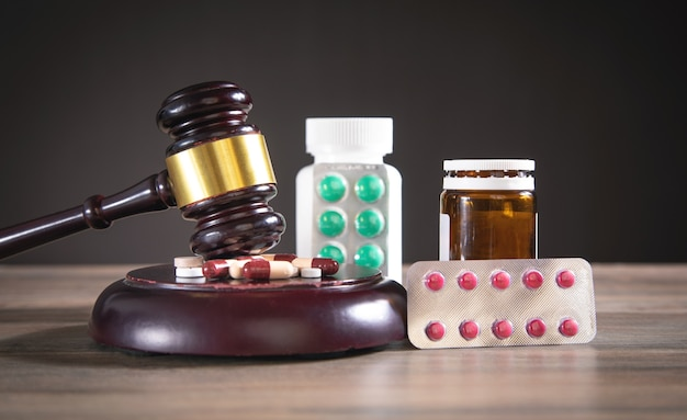 Judge gavel with pills on the wooden table.