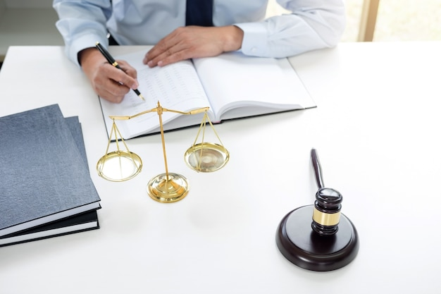 Judge gavel with scales of justice, male lawyers working having at law firm in office