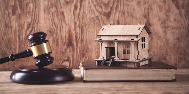 Judge gavel with a wooden house model.