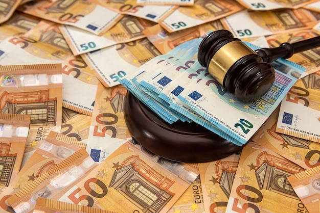Judge hammer on 50 euro banknotes background. court law