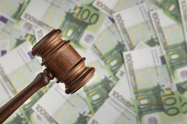 유로 지폐 배경에 판사 망치입니다. 판사는 돈에 대해 디노. 부패한 법원.